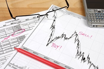 papeles, telefono, gafas y boli para hacer paper trading
